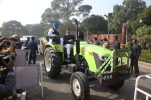 Dushyant Chautala riding a green tractor into the parliament